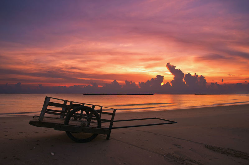 Cart On Shore At Beach Against Sky During Sunset