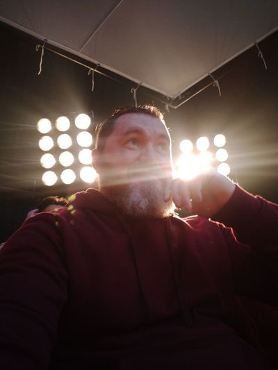 Portrait of man with illuminated lights in ceiling