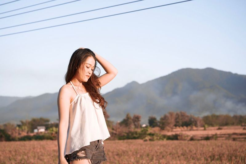 Fashionable young woman with hand in hair standing on land against sky