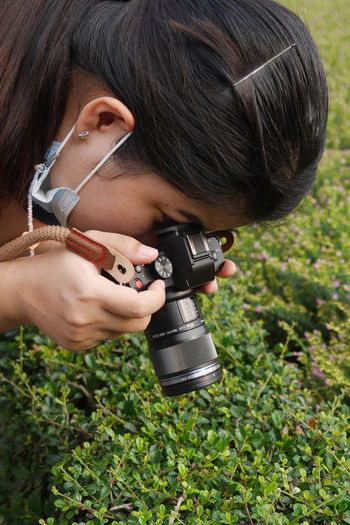 Portrait of woman holding camera on field
