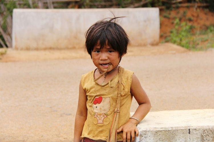 Portrait of poor girl standing on road