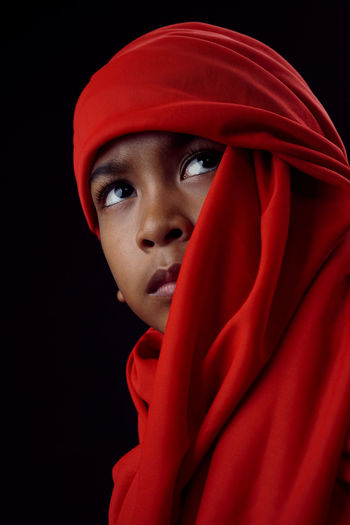 Boy wearing red textile against black background
