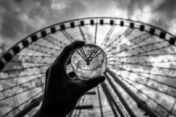 Cropped hand of person holding crystal ball with reflection of ferris wheel