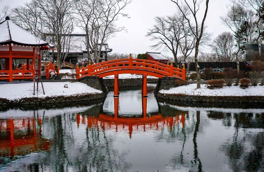 Japanese bridge in a snowy Samurai Village, Hokkaido, Japan. Japan Samurai Village Reflection Water Outdoors Bridge Snow Orange Color Nature Architecture Built Structure Symmetry Hokkaido Hokkaido Japan Winter Spring Shades Of Winter
