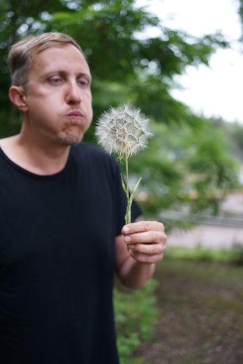Young man holding dandelion flower