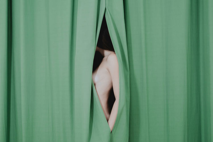 Midsection of naked woman hiding behind curtain