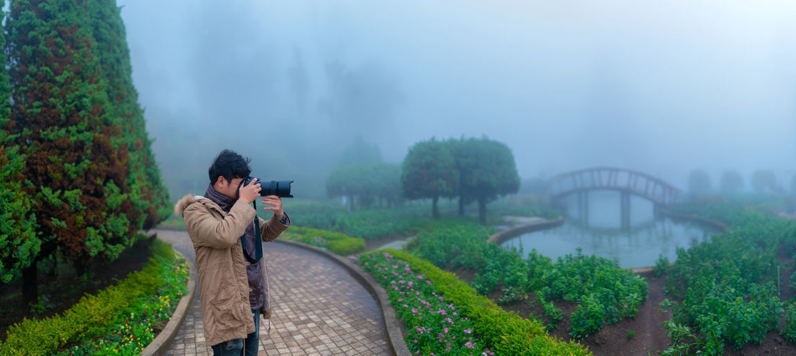 Landscape misty panorama , photographer taking pictures of foggy garden Camera Activity Fog Photographic Equipment Nature Architecture Digital Camera Photographer Outdoors Backgrounds Landscape Mist Panorama Garden Garden Photography Foggy Foggy Weather Weather Winter Travel Tourism Mountain Forest Professional Professionalphotography