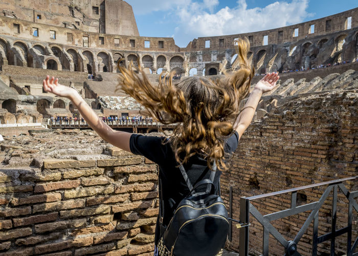 Rear view of girl with long hair at colosseum