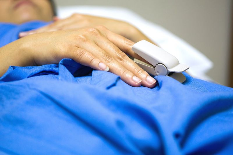 Close-Up Of Midsection Of Patient Lying On Hospital Bed