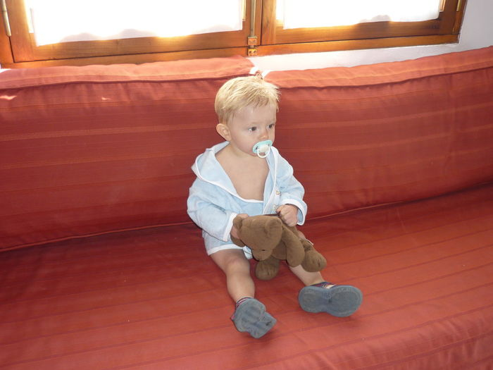 Baby boy with pacifier in mouth sitting on sofa at home