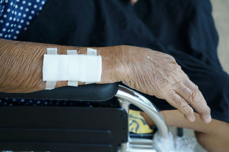 Close-up of senior woman with injured hand on wheelchair