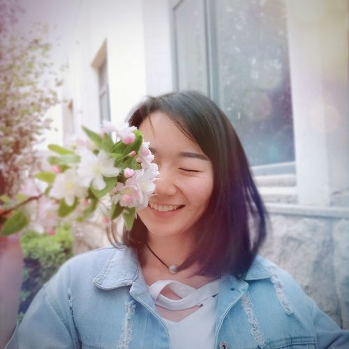 Smiling Young Woman Standing By White Flowering Plants