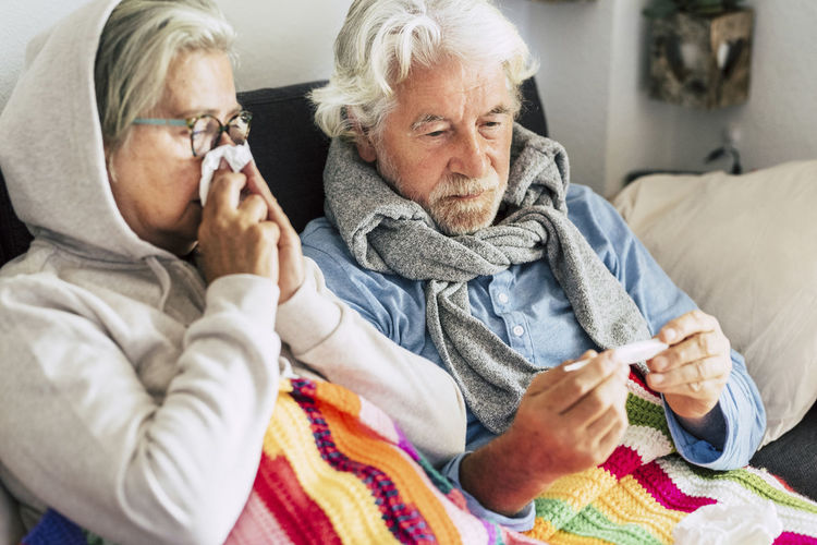 Close-up of senior man holding thermometer while sitting with wife on sofa at home