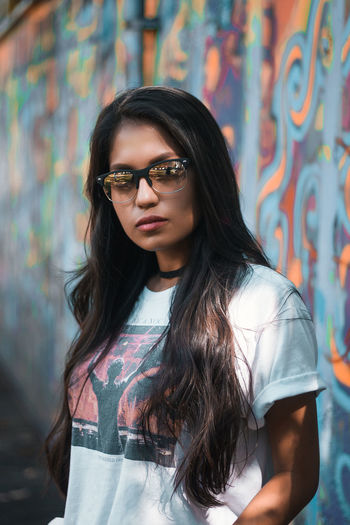 Portrait of young woman wearing sunglasses standing against wall