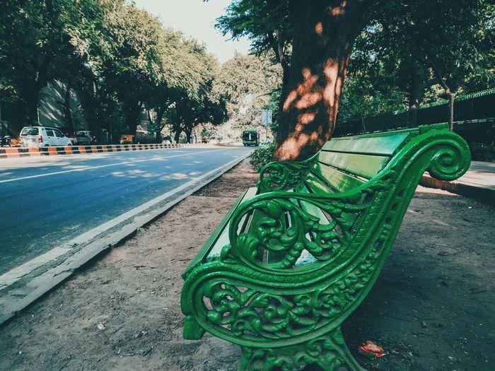 Empty bench by street in park