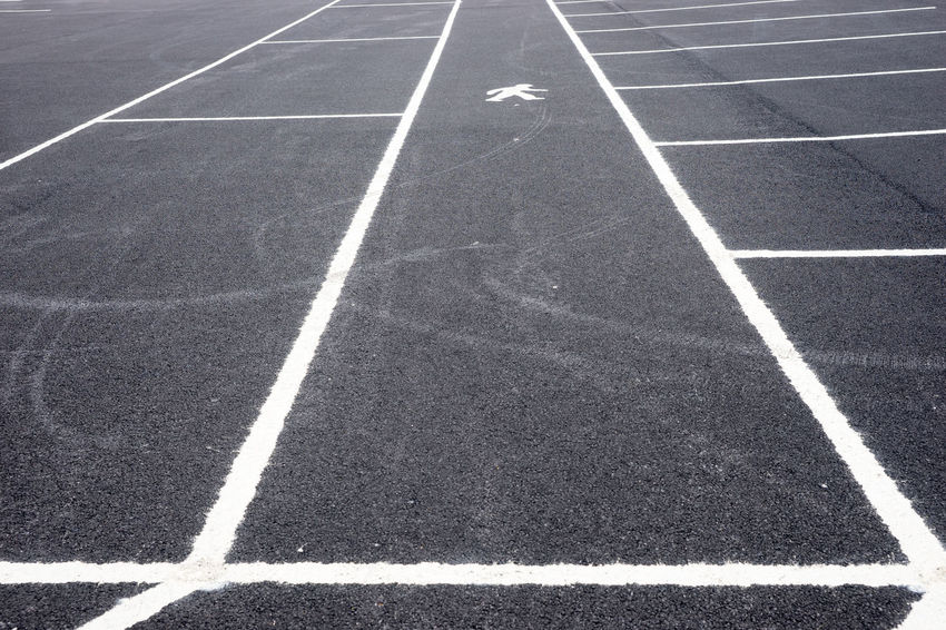 Empty parking lot with path for pedestrians Asphalt Lines Parking Lot Road Black Competition Day Empty High Angle View Marking Marking Of Road No People Nobody Outdoors Pathway Row Running Track Street Track And Field White Color