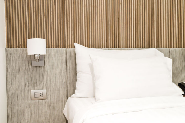 Electric lamp hanging by bed at hotel