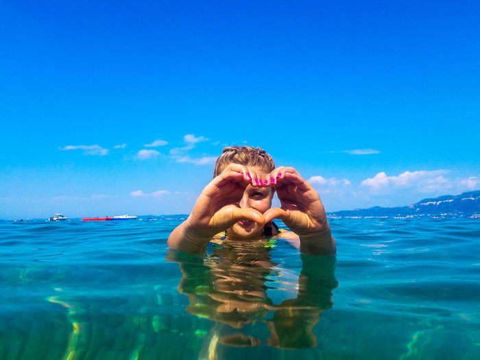 Woman making heart shape with hands in sea against blue sky during sunny day