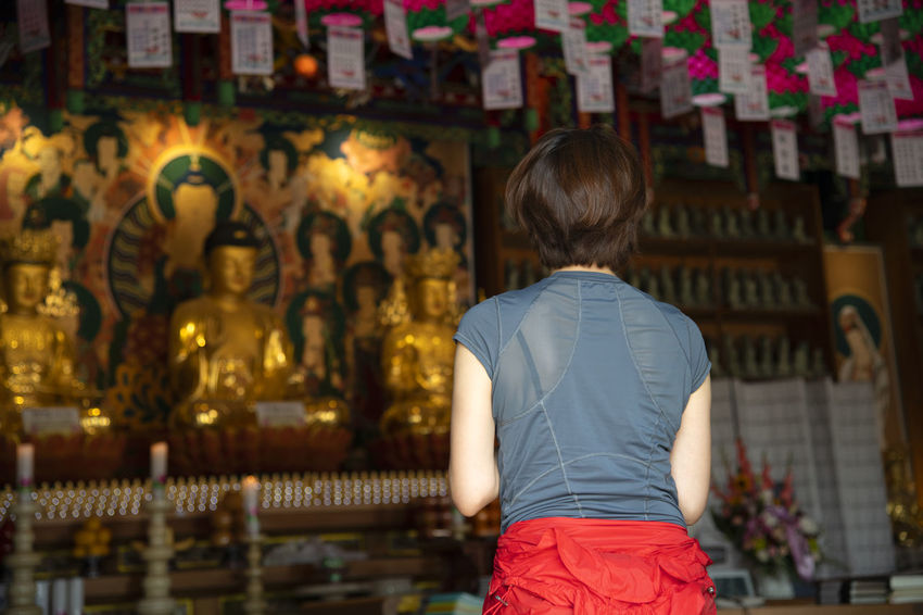 view of Bomunsa, a famous Buddhism temple in Seokmodo, Kimpo, Gyeonggido, South Korea Bomunsa Buddhism Temple Seokmodo Art And Craft Belief Buddhism Casual Clothing Creativity Ganghwado Hairstyle Human Representation Indoors  Leisure Activity Lifestyles One Person Place Of Worship Real People Rear View Religion Sculpture Spirituality Statue Temple Women