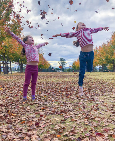 Girls jumping in autumn leaves Autumn Casual Clothing Change Child Childhood Day Females Field Full Length Girls Innocence Land Leaf Leaves Leisure Activity Nature Outdoors Park Plant Plant Part Positive Emotion Real People Sister Women