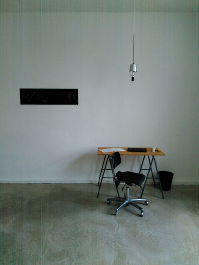 Empty Chair And Table Against Wall At Home