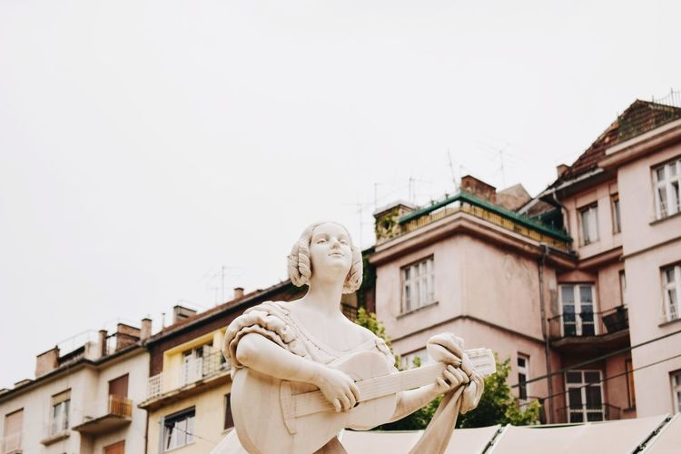 Low angle view of statue against building against clear sky