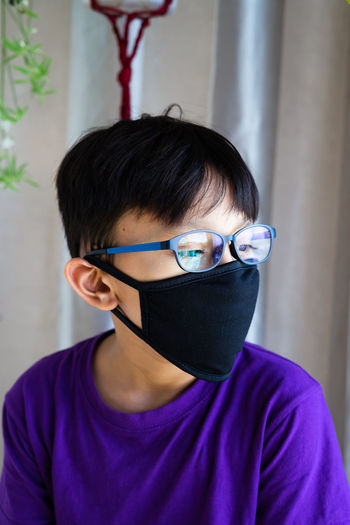 Close-up of girl wearing mask looking away