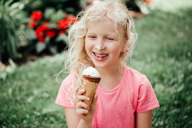 funny adorable girl with dirty nose and milk moustaches eating licking ice cream from waffle cone.