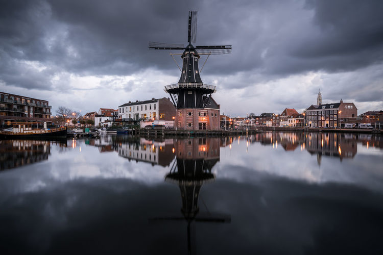 Reflection Of Traditional Windmill On River In City At Dusk