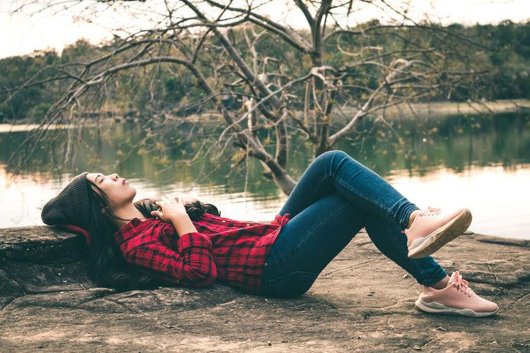 Woman relaxing at lakeshore
