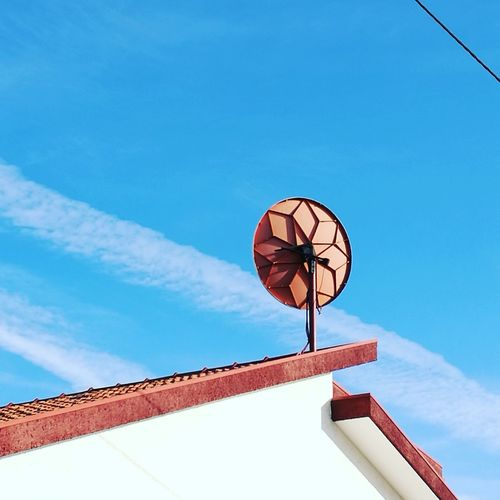 Low angle view of satellite dish on roof against sky