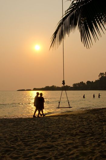 Silhouette People Walking By Rope Swing At Beach Against Sky During Sunset