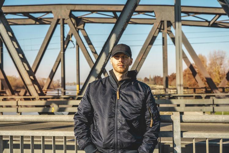 Portrait of man standing against bridge in city during winter
