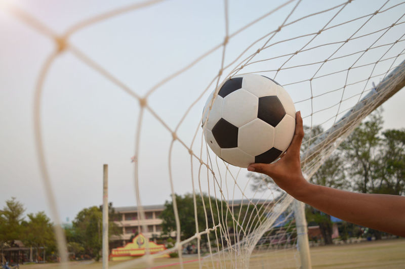 Hand playing soccer ball against sky