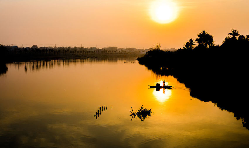 Beauty In Nature Lake Mode Of Transportation Nature Nautical Vessel Non-urban Scene Orange Color Outdoors Plant Reflection Rowing Scenics - Nature Silhouette Sky Sun Sunset Tranquil Scene Tranquility Transportation Tree Water Waterfront
