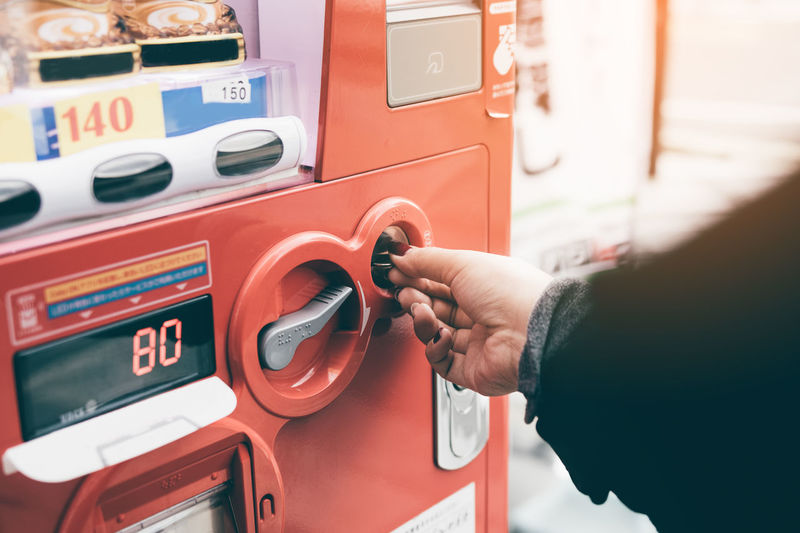 Cropped image of woman inserting coin in vending machine