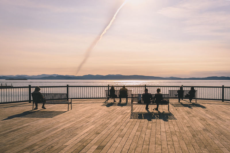 Enjoying the sunset on the pier in Burlington, Vermont After Work Beauty In Nature Bench Calm Evening Evening Sky Lake Landscape Lifestyles Mountain Nature Outdoors People Quiet Quiet Moments Real People Scenics Sea Silhouette Sky Sun Sunset Travel Water EyEmNewHere EyeEmNewHere The Secret Spaces Break The Mold
