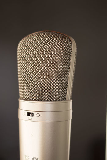 Close-up of microphone against gray background