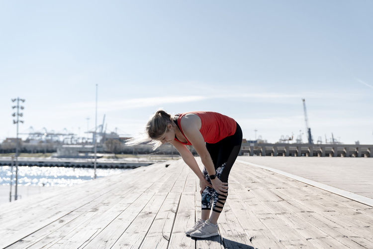 Woman standing on footpath by pier against sky