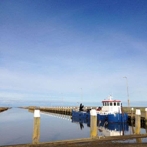 Fishing boat moored in canal at noordpolderzijl against sky