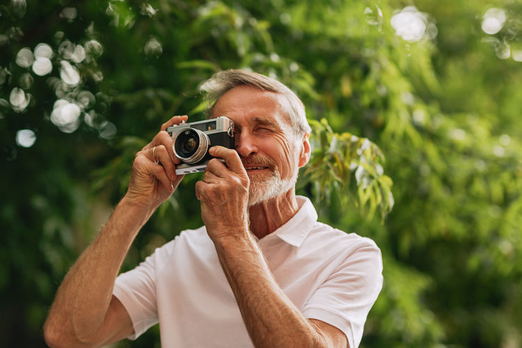 Smiling man holding camera outdoors