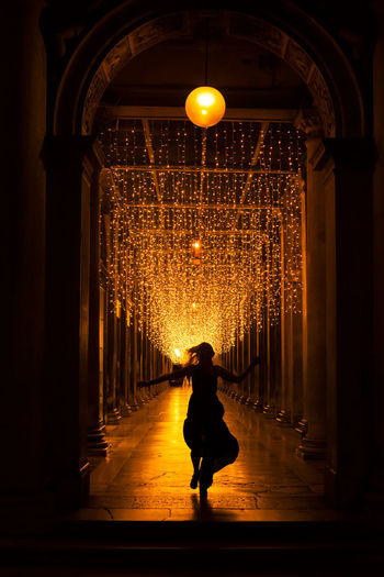 Full length of silhouette woman in illuminated corridor