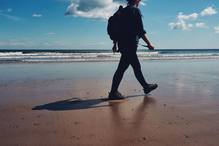 Low section of woman walking at beach against sky