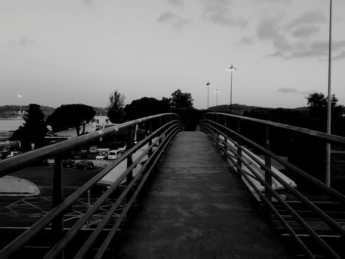 View of footbridge in city against sky