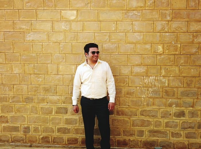 Smiling man standing against brick wall