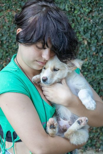 Woman embracing dog against plants