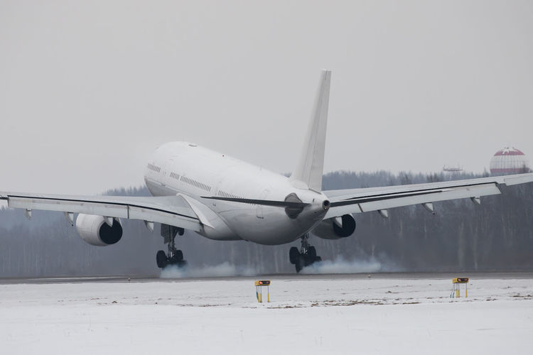 Airplane on runway against clear sky during winter