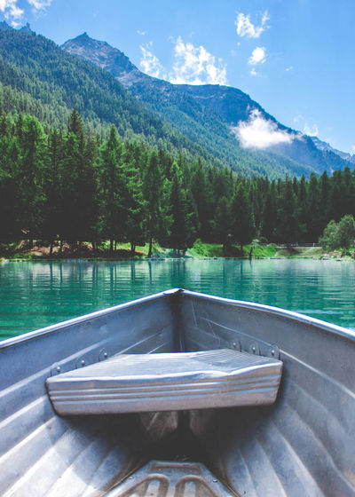 Boat moving on lake by mountains against sky