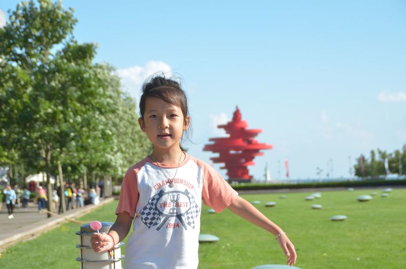 Portrait Of Girl Holding Candy While Standing At Park