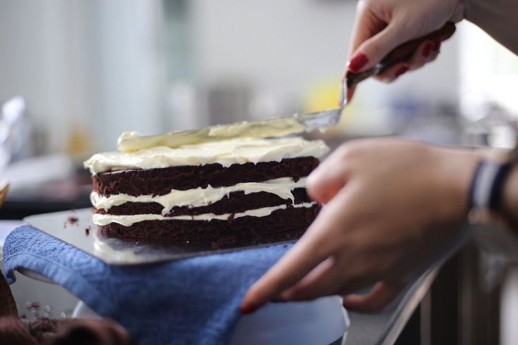Cropped image of woman hand icing cake in kitchen